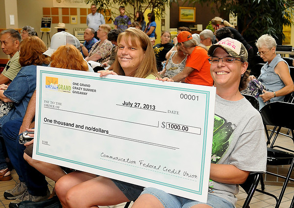 Kelly Ronistal and Neva Reese (from left) hold the $1,000 check that Ronistal won during the One Grand Crazy Summer Give Away at Oakwood Mall Saturday, July 27, 2013. (Staff Photo by BONNIE VCULEK)