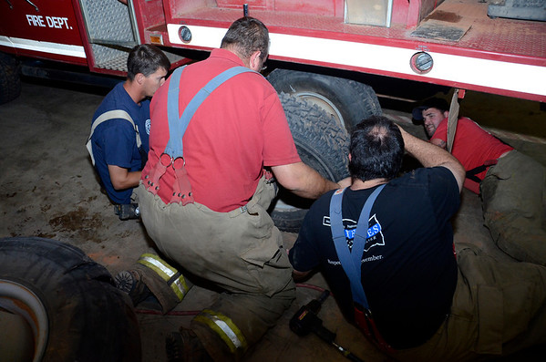 Waukomis Fire Department members fix a dual tire that blew out while they were en route to a fire. Pretending to be a pit crew, they raced the clock to make the repair. (Staff Photo by JESSICA SALMOND)