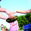 Keegan Bailey, left, lets his daughter Kymbree, 6, right, touch the turtle he accidentally caught at the fishing derby on July 4 at Meadowlake Park. Keegan removed the hook before releasing the turtle back into the water.(Staff Photo by JESSICA SALMOND)