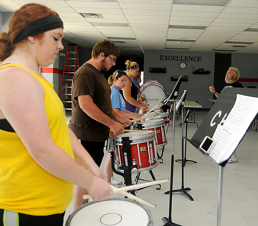 Tim Copeland (left) instructs the Chisholm High School Band drum line during the annual band camp Wednesday, July 24, 2013. Participants learn the new field marching and color guard routines, as well as musical selections for the fall competitions. (Staff Photo by BONNIE VCULEK)