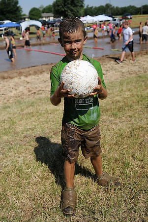 A young man enjoys the 2nd annual Miracle League Mud Volleyball action as he retrieves the balls for the 21 teams in the tournament Saturday, July 13, 2013. (Staff Photo by BONNIE VCULEK)