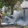 Captain James Milacek uses a booster hose to extinguish a shed fire behind the home at 615 E. Broadway Monday, July 1, 2013. The Enid Fire Department and Enid Police Department closed E. Broadway between the 500 and 700 blocks as firefighters worked the scene. (Staff Photo by BONNIE VCULEK)