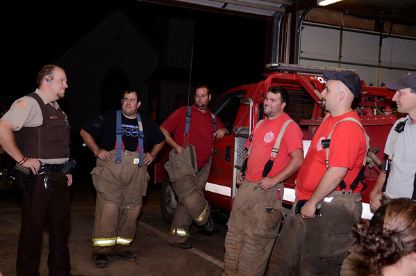 Members of the Waukomis Fire Department relax after answering call after call Thursday evening, July 4. The department always gathers at the station on July 4 to handle the many fire calls they receive. (Staff Photo by JESSICA SALMOND)