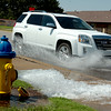 Water flows from a hydrant as a motorist drives through standing water on North Oakwood Road during city of Enid water line repairs Friday, July 25, 2014. (Staff Photo by BONNIE VCULEK)