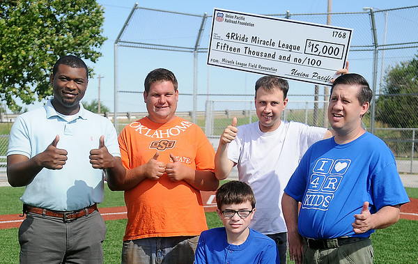 Brandon Morris (left), Director of Public Affairs for the Union Pacific Railroad in Oklahoma and Arkansas, gives a thumbs up with 4RKids Miracle League players (from left) Jeremy Clickner, Matthew Schultz, Travis Dunn and Joe Pankonin after Morris presented a $15,000 donation for additional renovations at AMBUCS ABC Park Wednesday, July 9, 2014. 4RKids Miracle League provides an opportunity for children and adults with special needs to play baseball during May and June each summer. (Staff Photo by BONNIE VCULEK)