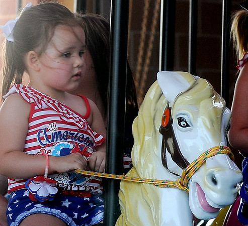 """An """"All American Girl"""" rides on the carousel at Meadowlake Park Friday, July 4, 2014. (Staff Photo by BONNIE VCULEK)"""