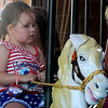 "An ""All American Girl"" rides on the carousel at Meadowlake Park Friday, July 4, 2014. (Staff Photo by BONNIE VCULEK)"
