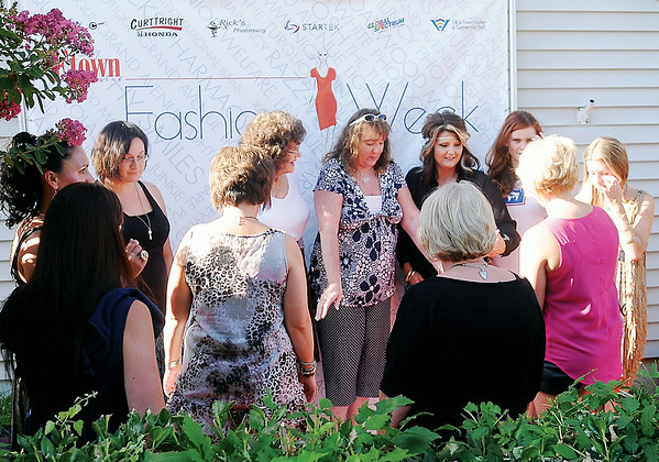 Ladies pause on the Etown Fashion Week red carpet outside Maple Place Bed & Breakfast during media night festivities Monday, July 7, 2014. Proceeds from the week-long events support Loaves & Fishes, the Northwest Oklahoma Regional Food Bank. (Staff Photo by BONNIE VCULEK)