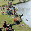 A young man tosses a stringer of catfish back into the lake as fishing enthusiasts line the north bank during the Fourth of July Fishing Derby at Meadowlake Park Friday, July 4, 2014. (Staff Photo by BONNIE VCULEK)