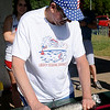 Larry Howard measures an 18.5 inch catfish caught by Dennis Hoopingarner during the Fourth of July fishing derby at Meadowlake Park Friday, July 4, 2014. (Staff Photo by BONNIE VCULEK)