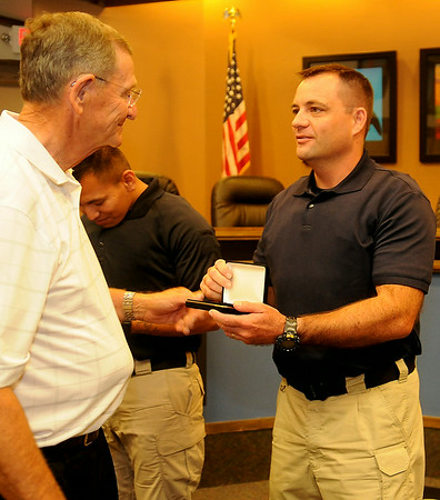 Enid Mayor Bill Shewey (left) congratulates new Enid Police Officer Nicholas Shackleford as he presents Shackleford with his EPD badges during a special swearing in ceremony at the city of Enid Commission Chambers Thursday, July 10, 2014. (Staff Photo by BONNIE VCULEK)