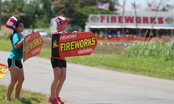 Kaylyn Marr and Kamryn Theilen (from left) dance on the corner of Garland and Willow Roads as they atrack individuals to TNT Fireworks Thursday, July 3, 2014. For the last three years, Central Assembly of God has run the large stand with proceeds funding mission and youth projects. (Staff Photo by BONNIE VCULEK)