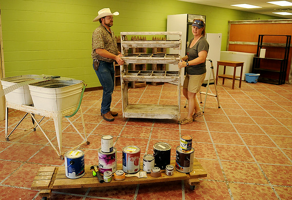 Gary and Paulette Rink arrange furnishings inside the new, expanded business location for Rowdy Stickhorse at Indian Hills Shopping Center Saturday, July 5, 2014. The Rinks, who farm near Covington, have been the local food connection for healthier products over the last six years at Enid Farmers Market and several Stillwater and Oklahoma City locations. (Staff Photo by BONNIE VCULEK)