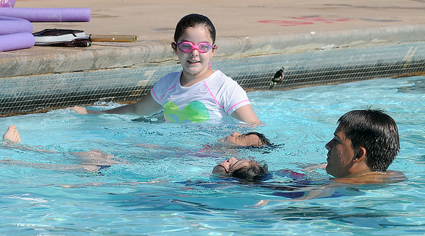 Joel Davis teaches young swimmers how to float on their backs during morning swim lessons at Champlin Pool Tuesday, July 15, 2014. (Staff Photo by BONNIE VCULEK)
