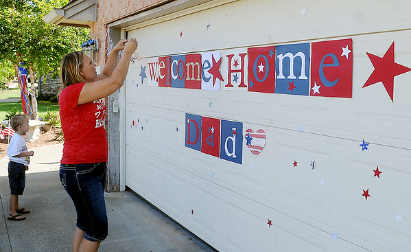 Larissa Bragg hangs decorations outside her home before she and her four children depart Enid to welcome Capt. Joel Bragg at Will Rogers Airport in Oklahoma City Friday, July 4, 2014. Capt. Bragg, who is stationed at Vance Air Force Base, returns after serving a one-year tour of duty in Afghanistan. (Staff Photo by BONNIE VCULEK)