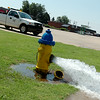 Water flows from a hydrant on North Oakwood Road as city of Enid crews complete water line repairs Friday, July 25, 2014. (Staff Photo by BONNIE VCULEK)