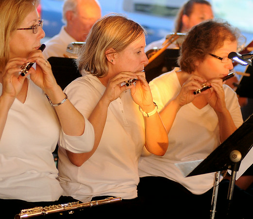 Juliana Overmier, Elizabeth Allen and Becky Buller (from left) play piccolo during the Enid Symphony Orchestra performance at the Fourth of July fireworks extravaganza at Meadowlake Park Friday, July 4, 2014. (Staff Photo by BONNIE VCULEK)