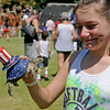 Cheyenne Daniel holds Sam, her patriotic turtle that finished second, during the Hometown Celebration turtle race at Adventure Quest Friday, July 4, 2014. (Staff Photo by BONNIE VCULEK)