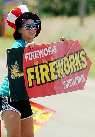Kaylyn Marr dons patriotic glasses and hat as she attracts individuals to TNT Fireworks Thursday, July 3, 2014. For the last three years, Central Assembly of God has sold fireworks for Fourth of July celebrations. The proceeds from the sales support mission and youth projects throughout the year. (Staff Photo by BONNIE VCULEK)