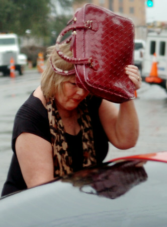 Cathy Nulph shields her face from moderate rainfall as she unlocks her car Wednesday, July 30, 2014. (Staff Photo by BONNIE VCULEK)