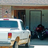 Oklahoma Highway Patrol, Garfield County Sheriff Department and Enid Police Department sealed off the entrance to Sunridge Estates after pursuing a motorcyclist who rode in and out of traffic, including the wrong way on Van Buren during lunchtime Friday, July 25, 2014. The man, who was riding the motorcycle (right) shown inside the garage, was apprehended at 841 Sunridge Estates. (Staff Photo by BONNIE VCULEK)