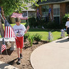"Clark Bragg (left) places American flags in his yard as Conner, Lilian, Larissa and Kalee (right) prepare a ""We Stand United"" banner at 1121 Briar Ridge Friday, July 4, 2014. Larissa Bragg and her four children left Enid this morning for Will Rogers Airport in Oklahoma City to welcome home Capt. Joel Bragg, who has been on a one-year tour of duty in Afghanistan. (Staff Photo by BONNIE VCULEK)"