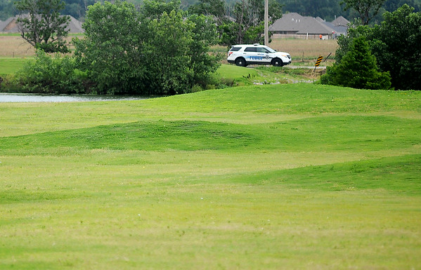 An Enid Police officer patrols Garland Road near Pheasant Run Golf Course Wednesday, July 3, 2014. Rick Childs faces six counts of assault with a dangerous weapon after firing on Enid Police officers in the 1300 block of Garland Road. (Staff Photo by BONNIE VCULEK)