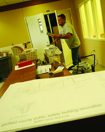 Jim Reese, from Reese Construction, installs interior door hardware at the Garfield County Public Safety Building Wednesday, July 16, 2014. The renovation at the facility should be completed by September. (Staff Photo by BONNIE VCULEK)