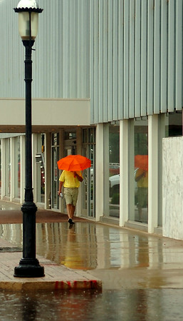 A gentleman's reflection appears in a Security National Bank window as rain falls early Wednesday, July 30, 2014. (Staff Photo by BONNIE VCULEK)
