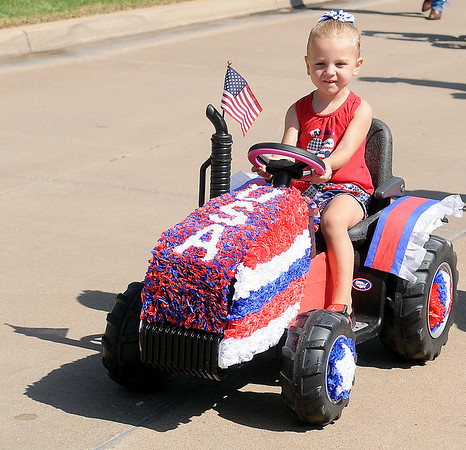 A young lady's tractor sports U.S.A. red, white and blue decorations during the Wilderness Cove neighborhood parade Friday, July 4, 2014. (Staff Photo by BONNIE VCULEK)