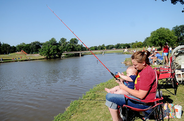 Brittany Smith helps Sebastian Jordan hold a rod and reel during the annual Fourth of July fishing derby at Meadowlake Park Friday, July 4, 2014. (Staff Photo by BONNIE VCULEK)