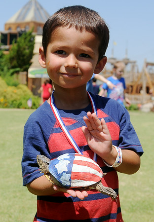 Kody Allison, 3, smiles as he holds his two-time turtle race champion at Leonardo's Children's Museum Hometown Celebration at Adventure Quest Friday, July 4, 2014. (Staff Photo by BONNE VCULEK)