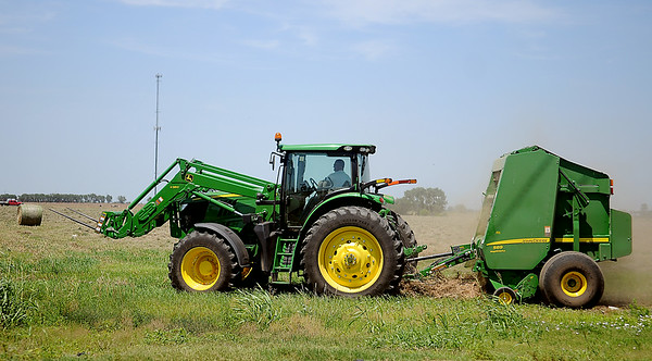 A farmer uses John Deere equipment as he bales hay in a field along West Willow Thursday, July 3, 2014. (Staff Photo by BONNIE VCULEK)