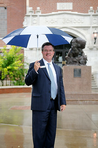 Dr. Darrell Floyd, the new superintendent at Enid Public Schools, uses an Enid Plainsmen umbrella as he pauses in the rain at Enid High School Thursday, July 17, 2014. (Staff Photo by BONNIE VCULEK)