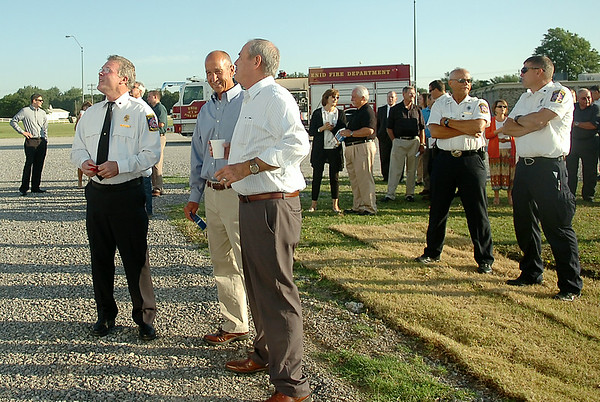 Enid Fire Chief Joe Jackson (left), other dignitaries and guests gather at the base of the new fire training tower at Autry Technology Center Tuesday, July 29, 2014. (Staff Photo by BONNIE VCULEK)