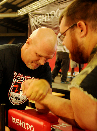 Jeff Adams (left) and Caleb Hand, both from Enid, warm up before they pull during the Bushido arm wrestling tournament at the Chisholm Trail Coliseum Saturday, July 12, 2014. (Staff Photo by BONNIE VCULEK)