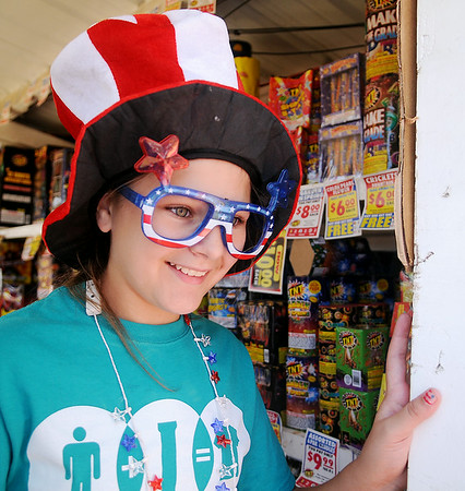 Kaylyn Marr dons patriotic glasses and hat as she assists individuals with their fireworks purchase at TNT Fireworks Thursday, July 3, 2014. (Staff Photo by BONNIE VCULEK)