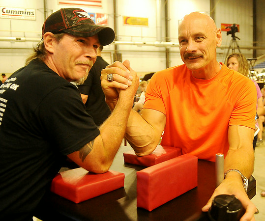 Allen Fisher (right), the twenty-six time world Bushido arm wrestling champion warms up for competition with another puller at the Chisholm Trail Coliseum Saturday, July 12, 2014. More than 150 entered the event hosted by Anew Church in Enid. (Staff Photo by BONNIE VCULEK)
