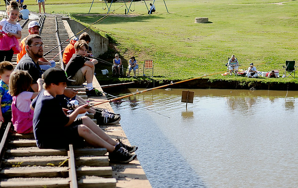 Fishing enthusiasts cast their bait into the lake at Meadowlake Park during the annual Fourth of July fishing derby Friday, July 4, 2014. (Staff Photo by BONNIE VCULEK)