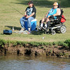 Jeff Jung (right) fishes with a friend during the annual Fourth of July fishing derby at Meadowlake Park Friday, July 4, 2014. (Staff Photo by BONNIE VCULEK)