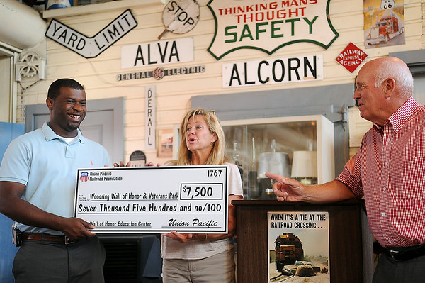 Connie Blankenship (center) and Doug Frantz (right) accept the Union Pacific Railroad Foundation $7,500 donation for the Wall of Honor and Veterans Park Education Center from Brandon Morris, Director of Public Affairs in Oklahoma and Arkansas for Union Pacific, during presentations at the Railroad Museum of Oklahoma Wednesday, July 9, 2014. A total of $22,500 was accepted by the Wall of Honor board members during the event. (Staff Photo by BONNIE VCULEK)