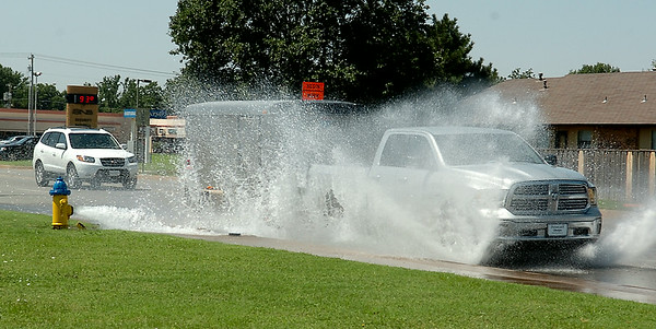 Drivers spray water into the air as a flowing hydrant creates a standing water issue on North Oakwood Road Friday, July 25, 2014. City of Enid employees were clearing debris from water lines after completing repairs between Randolph and Willow. (Staff Photo by BONNIE VCULEK)