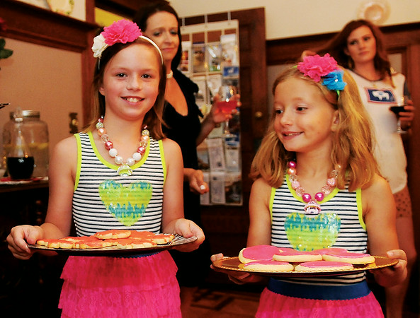 Jelani King and Lily Eckert (from left) offer sugar cookies to guests during the Etown Fashion Week media night at Maple Place Bed & Breakfast Monday, July 7, 2014. Proceeds from the week-long events support Loaves & Fishes, the Northwest Oklahoma Regional Food Bank. (Staff Photo by BONNIE VCULEK)