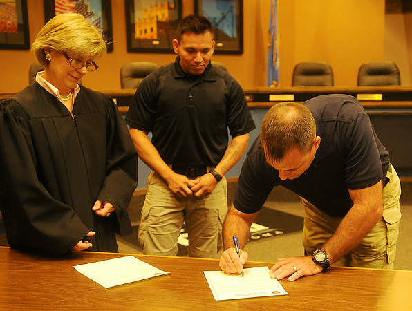 Judge Linda Pickens (left) presides over the swearing in ceremony for new Enid Police Officers Jesse Hernandez (back center) and Nicholas Shackleford (right) in the city of Enid Commission Chambers Thursday, July 10, 2014. (Staff Photo by BONNIE VCULEK)