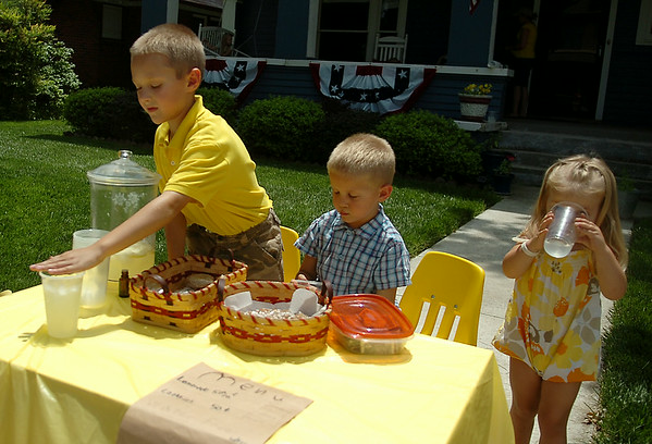 Isaac and Zach Piper (from left) serve refreshing homemade lemonade, chocolate chunk and oatmeal raisin cookies from their front yard lemonade stand Tuesday, July 29, 2014. The boys hope to earn enough money for a trip to Legoland during a California vacation in December. (Staff Phoot by BONNIE VCULEK)