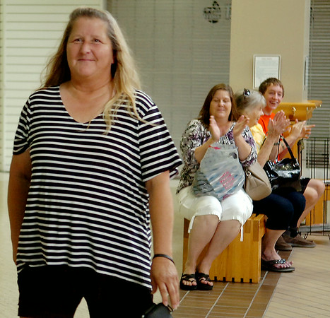 Ginger Cass, from Meno, reacts as she approaches the stage after winning One Grand Crazy Summer Giveaway's trip to Branson, sponsored by Enid Travel Consultants at Oakwood Mall Saturday, July 26, 2014. Cass and her family members (back right) who eat at Western Sizzlin all the time were pleased when her name was drawn. Peggy Base, who shops at Jumbos East on 30th Street, was the winner of the One Grand Crazy Summer Giveaway $1,000 check, sponsored by Communication Federal Credit Union. (Staff Photo by BONNIE VCULEK)