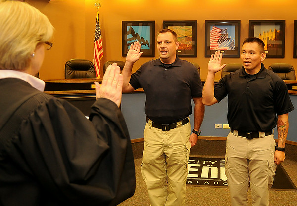 Judge Linda Pickens swears in new Enid Police Department officers, Nicholas Shackleford (center) and Jesse Hernandez (right) at a special ceremony inside the city of Enid Commission Chambers Thursday, July 10, 2014. (Staff Photo by BONNIE VCULEK)
