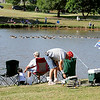 Fishing enthusiasts line the banks of Meadowlake Park during the annual Fourth of July fishing derby Friday, July 4, 2014. (Staff Photo by BONNIE VCULEK)