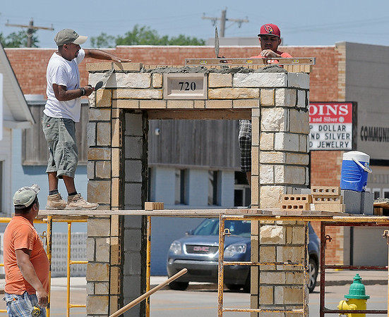 Masonry specialists check brick levels as they create a new business marquee at 720 W. Maine Monday, July 7, 2014. (Staff Photo by BONNIE VCULEK)