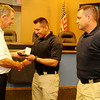 Enid Mayor Bill Shewey (left) presents new Enid Police Officers Jesse Hernandez (center) and Nicholas Shackleford (right) with their EPD badges during a special swearing in ceremony at the city of Enid Commission Chambers Thursday, July 10, 2014. (Staff Photo by BONNIE VCULEK)